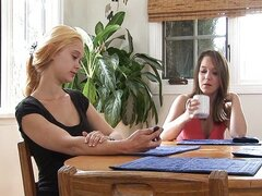 Chicas adolescentes haciendo hacia fuera en la mesa de la cocina