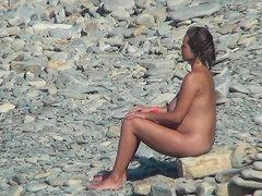 Morena bronceada está sentado en la piedra