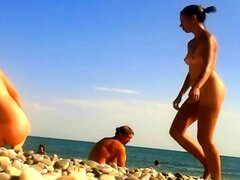 Nudist beach voyeur finds a sexy brunette enjoying the sun