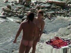 Mujer nudista con gafas de sol en la playa rocosa, nudista mujer con gafas de sol en la playa rocosa con su hombre goza el día.