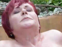 Abuela gordita jengibre golpeando al aire libre en casas de patio
