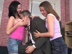 Dos chicas adolescentes sexy seducen a su viejo profesor de Universidad en su oficina