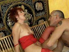 Abuela pelirroja en lencería recibiendo su clítoris estimulado por juguetes sexuales