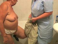 La enfermera baña a la abuelita gorda en el baño. La enfermera baña a la vieja abuelita gorda en el baño en casa