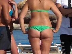 Chica en bikini verde con culo sexy, chica en bikini verde con culo sexy está en la playa.