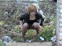 Milf losing off hose and panty and pissing outdoor, Sexy milf in a short dress and jacket was looking for a quiet place where she could lose sheer hose and panty down to the knees and sit pissing. Great voyeured movie from outdoor.