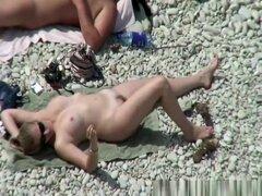 Par en el tipo de playa para tomar el sol, grasa el sol su cuerpo junto a su esposa. Ella va a tomar un baño en el agua y vuelve a su toalla a tomar el sol otra vez.
